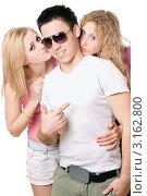 Купить «Две девушки нежно целуют юношу», фото № 3162800, снято 11 февраля 2010 г. (c) Сергей Сухоруков / Фотобанк Лори