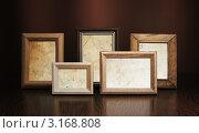 Купить «Пять фото рамок на деревянном столе на коричневом фоне», фото № 3168808, снято 20 февраля 2010 г. (c) vlntn / Фотобанк Лори