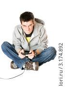 Купить «Молодой человек с джойстиком увлеченно играет», фото № 3174892, снято 5 февраля 2010 г. (c) Сергей Сухоруков / Фотобанк Лори