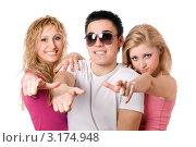 Купить «Две веселые девушки и парень вытянув руки, указывают вперед», фото № 3174948, снято 11 февраля 2010 г. (c) Сергей Сухоруков / Фотобанк Лори