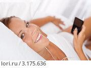 Купить «Улыбающаяся девушка в наушниках держит в руке mp3-плеер», фото № 3175636, снято 7 августа 2009 г. (c) CandyBox Images / Фотобанк Лори