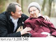 Пожилая женщина в инвалидной коляске на прогулке и ее заботливый сын. Стоковое фото, фотограф Дмитрий Калиновский / Фотобанк Лори
