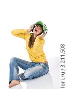 Купить «Сидящая счастливая девушка в джинсах слушает музыку», фото № 3211508, снято 11 марта 2010 г. (c) CandyBox Images / Фотобанк Лори