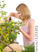 Купить «Счастливая блондинка опрыскивает растения», фото № 3213812, снято 30 апреля 2010 г. (c) CandyBox Images / Фотобанк Лори