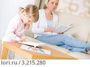Купить «Девочка набирает номер на телефоне в гостиной, а мама лежит на диване», фото № 3215280, снято 21 мая 2010 г. (c) CandyBox Images / Фотобанк Лори
