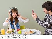 Парень фотографирует девушку в наушниках на мобильный телефон во время обеденного перерыва. Стоковое фото, фотограф CandyBox Images / Фотобанк Лори