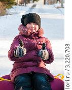Купить «Девочка сидя на тюбинге показывает что всё будет хорошо», эксклюзивное фото № 3220708, снято 29 января 2012 г. (c) Игорь Низов / Фотобанк Лори