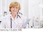 Купить «Женщина-врач улыбается и держит в руке клипборд», фото № 3223196, снято 11 октября 2011 г. (c) Raev Denis / Фотобанк Лори