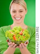 Купить «Улыбающаяся девушка держит овощной салат», фото № 3229892, снято 5 января 2011 г. (c) CandyBox Images / Фотобанк Лори