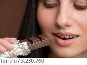 Купить «Девушка ест темный шоколад», фото № 3230760, снято 4 февраля 2011 г. (c) CandyBox Images / Фотобанк Лори