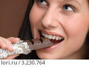Купить «Радостная девушка ест темный шоколад», фото № 3230764, снято 4 февраля 2011 г. (c) CandyBox Images / Фотобанк Лори