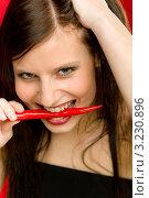 Купить «Страстная девушка кусает красный перец чили», фото № 3230896, снято 4 февраля 2011 г. (c) CandyBox Images / Фотобанк Лори