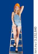 Девушка в строительной каске и джинсовом комбинезоне стоит на стремянке на синем фоне. Стоковое фото, фотограф Яков Филимонов / Фотобанк Лори