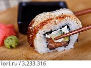 Ролл с угрём и лососем берут палочками для еды с бамбукового блюда. Стоковое фото, фотограф Наталия Китаева / Фотобанк Лори