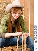 Купить «Портрет улыбающейся молодой девушки в ковбойской шляпе, с веревками в руках», фото № 3243308, снято 30 марта 2011 г. (c) CandyBox Images / Фотобанк Лори