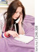 Молодая темноволосая девушка набирает номер на телефоне, лежа на кровати. Стоковое фото, фотограф CandyBox Images / Фотобанк Лори