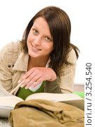 Купить «Улыбающаяся школьница делает уроки, лежа на полу», фото № 3254540, снято 21 сентября 2011 г. (c) CandyBox Images / Фотобанк Лори
