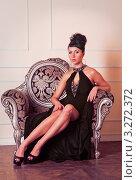 Девушка брюнетка в вечернем черном платье сидит на диване. Стоковое фото, фотограф Симон Герреро Ушаков / Фотобанк Лори