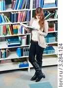 Купить «Студентка стоит в библиотеке с открытой книгой», фото № 3284124, снято 16 декабря 2018 г. (c) Дмитрий Калиновский / Фотобанк Лори