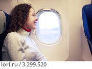 Купить «Красивая молодая девушка смотрит в иллюминатор самолета», фото № 3299520, снято 29 декабря 2009 г. (c) Losevsky Pavel / Фотобанк Лори