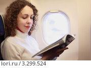 Купить «Молодая женщина с журналом в руках сидит в самолете у иллюминатора», фото № 3299524, снято 29 декабря 2009 г. (c) Losevsky Pavel / Фотобанк Лори