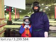 Купить «Мальчик с тренером по картингу стоят в шлемах на фоне трассы», фото № 3299584, снято 21 февраля 2011 г. (c) Losevsky Pavel / Фотобанк Лори