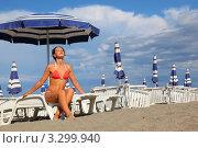 Купить «Молодая женщина сидит на пляже на шезлонге и загорает», фото № 3299940, снято 26 июля 2010 г. (c) Losevsky Pavel / Фотобанк Лори