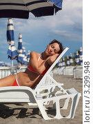 Купить «Улыбающаяся молодая женщина в красном купальнике лежит на шезлонге на пляже, закрыв глаза», фото № 3299948, снято 26 июля 2010 г. (c) Losevsky Pavel / Фотобанк Лори