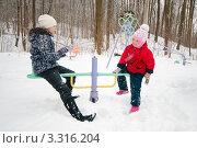 Купить «Маленькая и девочка подросток  качаются на качелях зимой», эксклюзивное фото № 3316204, снято 26 февраля 2012 г. (c) Игорь Низов / Фотобанк Лори
