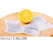 Купить «Половина лимона и пакетики чая на деревянной круглой доске», фото № 3362208, снято 22 февраля 2012 г. (c) Ivan Korolev / Фотобанк Лори