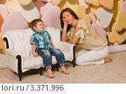 Мама рядом с сыном, сидящем на диване. Стоковое фото, фотограф Сергей Высоцкий / Фотобанк Лори