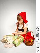 Девочка читает книгу с корзиной красных яблок в костюме красной шапочки (2011 год). Редакционное фото, фотограф Юлия Гусакова / Фотобанк Лори