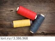 Купить «Разноцветные нитки для шитья в катушках на деревянной доске», фото № 3386968, снято 3 февраля 2011 г. (c) Олег Жуков / Фотобанк Лори