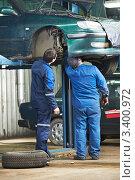 Купить «Два  автомеханика осматривают  автомобиль на станции техобслуживания», фото № 3400972, снято 31 марта 2012 г. (c) Дмитрий Калиновский / Фотобанк Лори