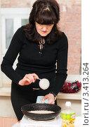 Купить «Женщина готовит блины  на переносной плите», эксклюзивное фото № 3413264, снято 25 февраля 2012 г. (c) Игорь Низов / Фотобанк Лори