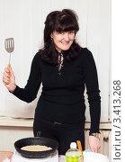 Купить «Счастливая женщина готовит блины  на переносной плите», эксклюзивное фото № 3413268, снято 25 февраля 2012 г. (c) Игорь Низов / Фотобанк Лори
