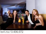 Купить «Веселые друзья смотрят в сторону, сидя за столиком в ночном клубе», фото № 3436072, снято 5 сентября 2010 г. (c) Андрей Попов / Фотобанк Лори