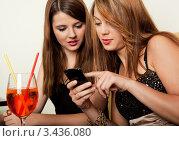 Две симпатичные подруги что-то рассматривают на мобильном телефоне. Стоковое фото, фотограф Андрей Попов / Фотобанк Лори