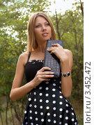 Купить «Красивая девушка в летнем сарафане с сумочкой в руках на фоне природы», фото № 3452472, снято 9 сентября 2010 г. (c) Сергей Сухоруков / Фотобанк Лори