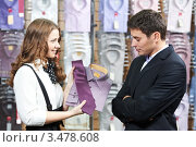 Купить «Девушка-продавец подбирает мужчине галстук к рубашке в магазине», фото № 3478608, снято 21 февраля 2012 г. (c) Дмитрий Калиновский / Фотобанк Лори