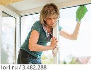 Женщина блондинка среднего возраста моет  окно. Стоковое фото, фотограф Игорь Низов / Фотобанк Лори