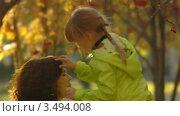 Девочка стряхивает листья с головы мамы. Стоковое видео, видеограф Павел Меняйло / Фотобанк Лори