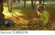 Женщина собирает опавшие листья вокруг девочки. Стоковое видео, видеограф Павел Меняйло / Фотобанк Лори