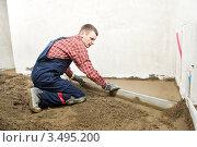 Купить «Строитель выравнивает пол в доме», фото № 3495200, снято 19 апреля 2012 г. (c) Дмитрий Калиновский / Фотобанк Лори