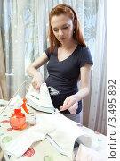 Купить «Беременная женщина дома гладить детскую одежду», фото № 3495892, снято 10 марта 2012 г. (c) Михаил Иванов / Фотобанк Лори