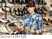 Женщина выбирает босоножки в магазине (2012 год). Редакционное фото, фотограф Игорь Низов / Фотобанк Лори