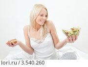 Купить «Светловолосая девушка не может выбрать между салатом и пончиком», фото № 3540260, снято 18 декабря 2011 г. (c) Андрей Попов / Фотобанк Лори