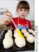 Купить «Маленькая девочка смазывает пирожки», фото № 3544976, снято 24 мая 2012 г. (c) Ольга Денисова / Фотобанк Лори