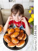 Купить «Счастливая девочка сидит за столом с пирожками», фото № 3544996, снято 24 мая 2012 г. (c) Ольга Денисова / Фотобанк Лори