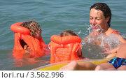 Купить «Мама с тремя детьми в спасательных жилетах на надувном матрасе в море», видеоролик № 3562996, снято 22 января 2010 г. (c) Losevsky Pavel / Фотобанк Лори